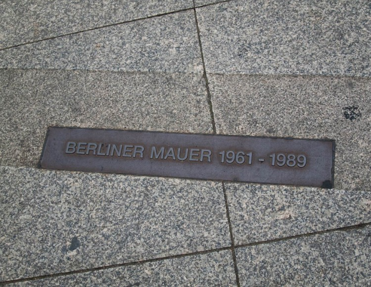 The position of the Berlin Wall is marked throughout the city, even though it doesn't exist anymore--a line drawn through buildings, across streets, behind the Brandenburg Gate.