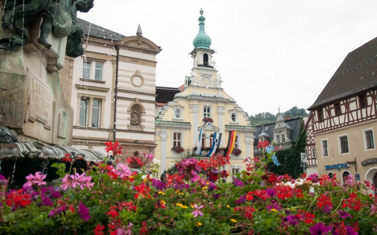 The courthouse on the town square, with the flags of Bavaria, Kulmbach, and Germany.